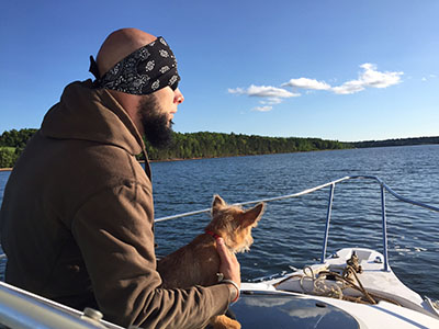 man holding dog in a boat on water